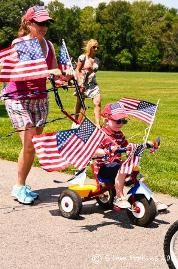 Young boy on his tricycle with American Flags attached