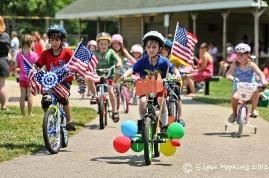 Kids riding their bikes with American Flags attached