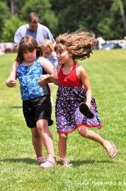 Two young girls racing with their legs tied together