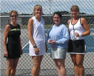 Four women in front of a fence in sports gear