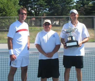 Three men by a tennis net, one holding a trophy