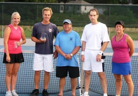 Two women and three men in front of a tennis net