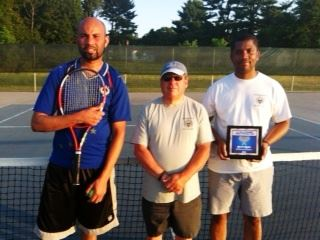 Three men, one holding a tennis raquet, one holding an award