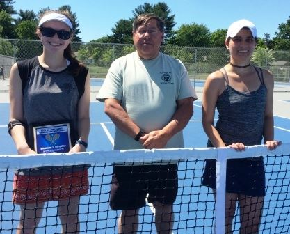 Two women and a man behind a tennis net